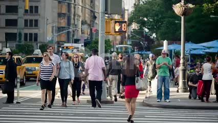 people crossing street at crosswalk on summer day on 5th Avenue in Manhattan