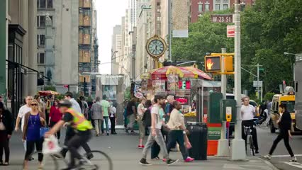 people walking on 5th Avenue in summer on sunny day with cars driving by, clock in background