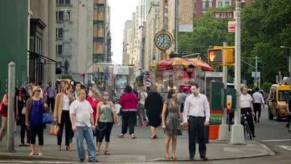 people walking on 5th Ave in Manhattan with clock in background