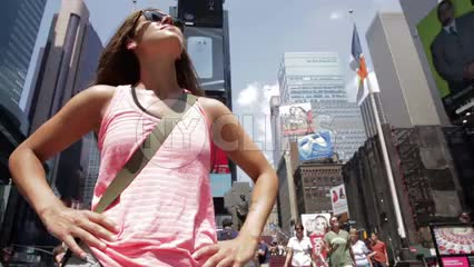female tourist with sunglasses looking up at overwhelming Times Square scenery - buildings and skyscrapers on sunny summer day