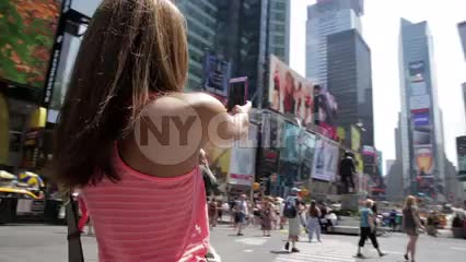 woman with sunglasses taking selfie in middle of Times Square on bright sunny day in summer