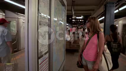 female tourist in pink tanktop and shorts in subway station looking at map