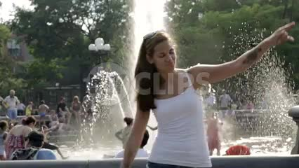 crazy girl dancing in Washington Square Park in front of water fountain sprinkler on summer day
