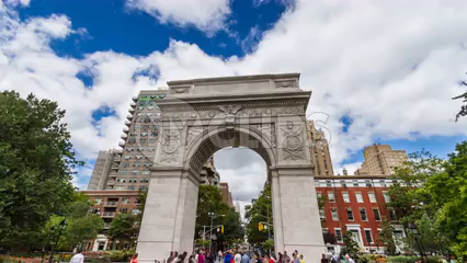 Washington Square Park arch and people in summer with beautiful blue sky and clouds - 4K timelapse in Greenwich Village NYC