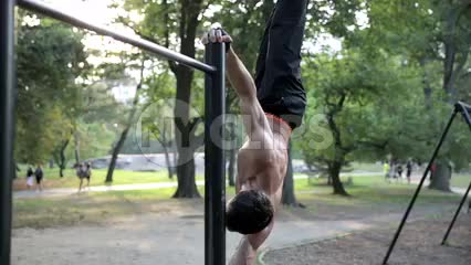 man bracing body on side with Central Park pull-up bar on summer day