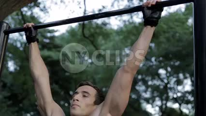 muscular man doing pull-ups in Central Park - athletic gymnast doing gymnastics on bar
