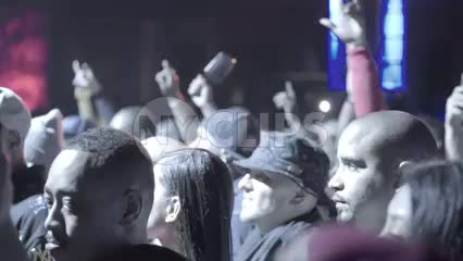 fans having fun at rap show - hip hop crowd in slow motion under smoky bright lights in slow motion
