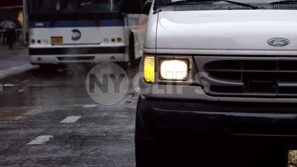 van in rain with MTA bus and woman with umbrella on rainy day in slow motion