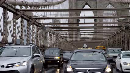cars driving in traffic on Brooklyn Bridge in rain, windshield wipers on rainy day - raining in slow motion