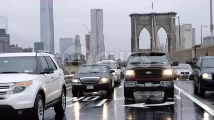 truck and cars entering Brooklyn from Bridge with Freedom Tower in background