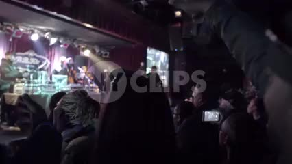closeup of fans in crowd cheering - standing in concert - watching hip hop music show interior venue