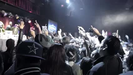 crowd with hands and arms in the air enjoying hip hop music concert - rap fans standing