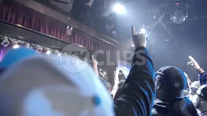 big crowd at hip hop show under bright lights - fans facing stage with hands in the air - slow motion