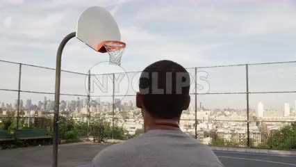 kid taking jump shot and scoring - basketball court overlooking Manhattan skyline
