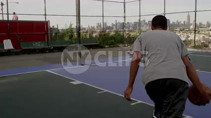 kid driving to basket and scoring finger-roll layup - outdoor basketball court in New Jersey with Manhattan skyline through fence