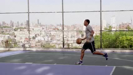 kid dribbling toward basket and shooting and scoring layup on basketball courts outside with Manhattan skyline in background through fence