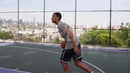 teenager dribbling up to basket and scoring layup - New Jersey basketball court overlooking Manhattan skyline through fence