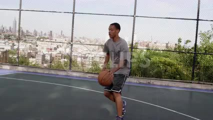 young athlete driving to basket and scoring layup - practicing basketball on outdoor court in summer