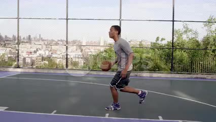 kid scoring beautiful layup practicing basketball on New Jersey courts in summertime