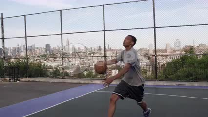 kid jumping up scoring layup on basketball court with view of Manhattan skyline through fence