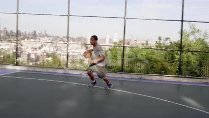 kid dribbling to basket and scoring reverse layup with left hand on basketball court with Manhattan skyline view in summer
