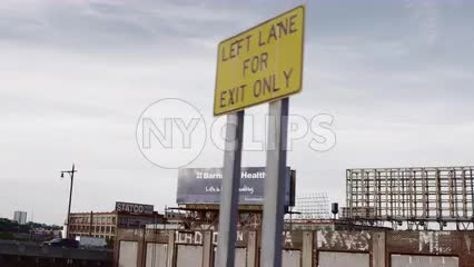 left lane for exit only sign in Brooklyn with gritty buildings with vandalism from driving car view