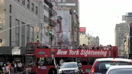 New York Sightseeing red tour bus turning corner on busy street