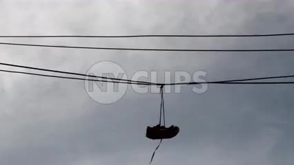 shoes hanging from wire - silhouette of sneakers on line