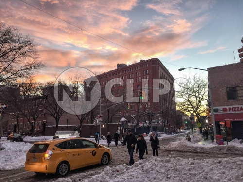 caravan taxicab on Lower East Side of Manhattan - people walking in snow - snowing at sunset in winter