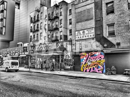 colorful graffiti piece on black and white street on Lower East Side of Manhattan in HDR