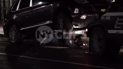 tow truck officer underneath car at night
