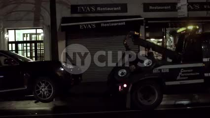 NYPD tow truck towing parked car at night