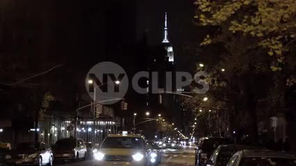 taxi cab on lower 5th Ave with Empire State Building in background at night