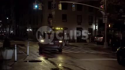 NYPD tow truck turning corner at night - towing car