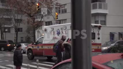 FDNY emergency ambulance truck driving down street on rainy day - view from under scaffolding