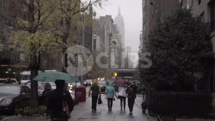 gloomy day raining on Lower 5th Avenue with people walking with umbrellas in Manhattan
