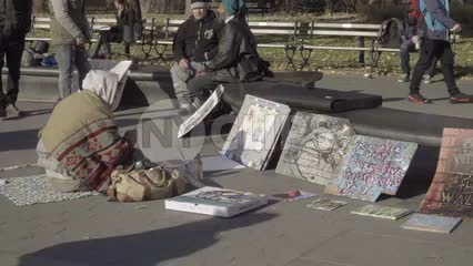 homeless artist selling art in Washington Square Park - bundled up on cold winter day
