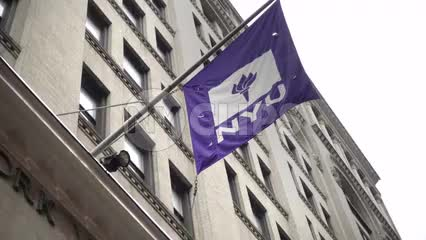 NYU flag on rainy day - raining at front doors of administrative university building - man entering