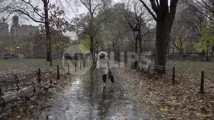 woman in coat walking in Washington Square Park in slow motion on wet rainy day in fall