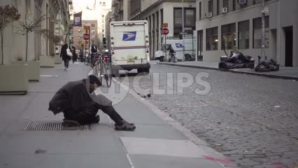 homeless man sitting on street in cold