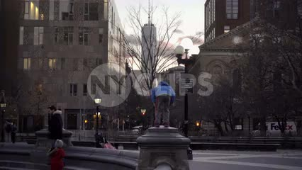 boy standing atop Washington Square Park circle with Freedom Tower at sunset on winter day