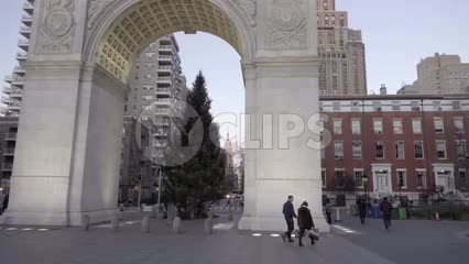 Christmas tree under Washington Square Park arch with Empire State Building in background on late afternoon day