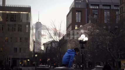 boy in Washington Square Park with view of Freedom Tower on cold winter day