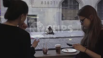 two women on smartphone in restaurant with black homeless man view through window in front of church