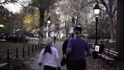 joggers in Washington Square Park on beautiful autumn day in slow motion