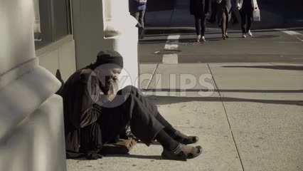 black man sitting on sidewalk on sunny day - homeless man