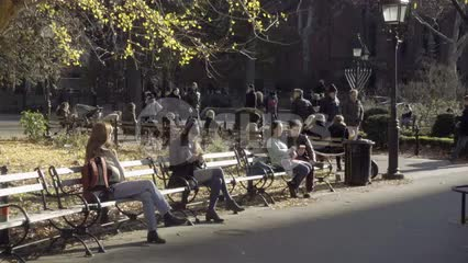people sitting on Washington Square Park bench - sunny day with benches