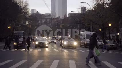 people crossing street in early evening on 6th ave with Freedom Tower in background