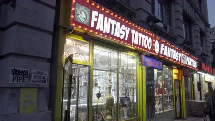 famous Fantasy Tattoo Party store sign with flashing lights on 6th ave in Greenwich Village in early evening