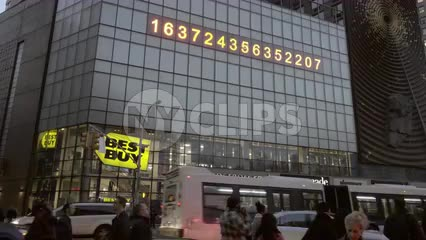 famous ticker numbers in Union Square with cars and people below on busy intersection - Best Buy, Nordstrom Rack, and Duane Reade store sign
